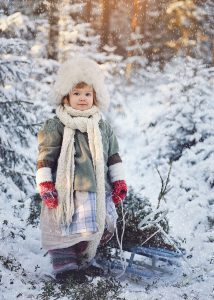 kuva tytöstä talvella metsässä auringonlaskun aikaan