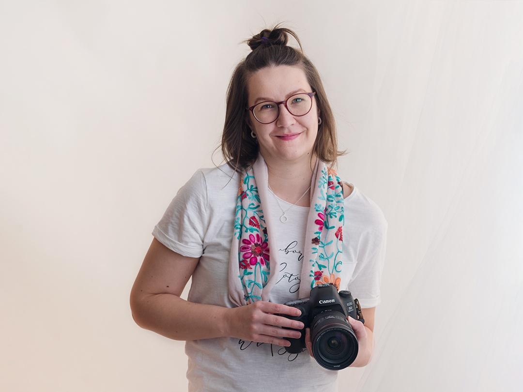 Kuva valokuvaajasta kamera kaulassa