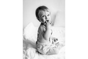 Mustavalkea kuva 1-vuotiaasta istumassa vaalealla peitolla