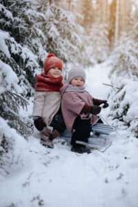 Sisarukset istuvat kelkassa talvella