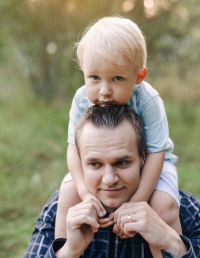 Isä & poika niityllä auringonlaskussa