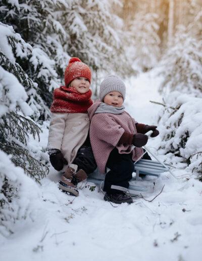 Sisarukset rattikelkan kyydissä talvisessa metsässä
