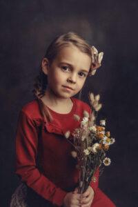 Tyttö kukkakimppu kädessä