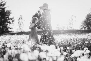 Tyttö ja nainen niityllä auringon laskiessa tanssivat käsi kädessä.